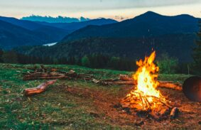 Campfire Burning In Front Of Mountains