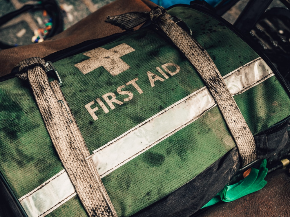 A green first aid kit used for outdoor recreation