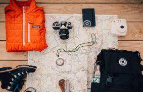 A backpack and boots with some of the essentials like a map and compass
