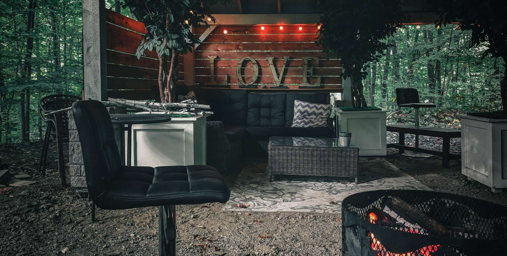 A glamping living space with comfortable furniture and a fire pit