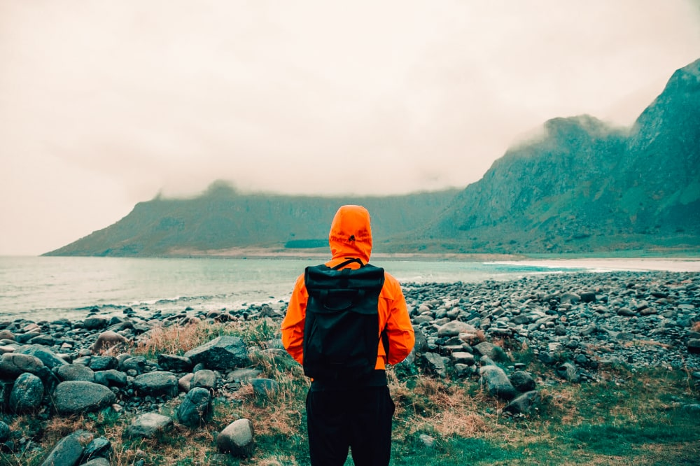 A person in an orange rain jacket looks at hills on a rocky shore