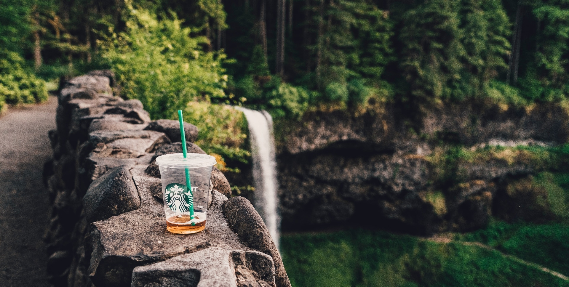 A carelessly discarded single-use Starbucks coffee cup litters the view