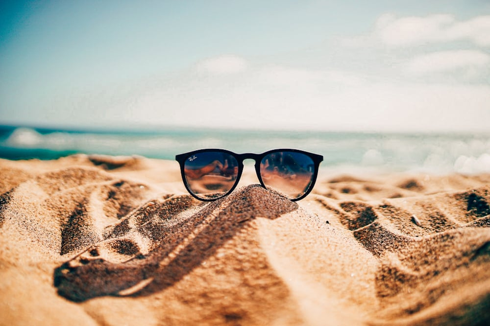A pair of sunglasses on a sandy beach