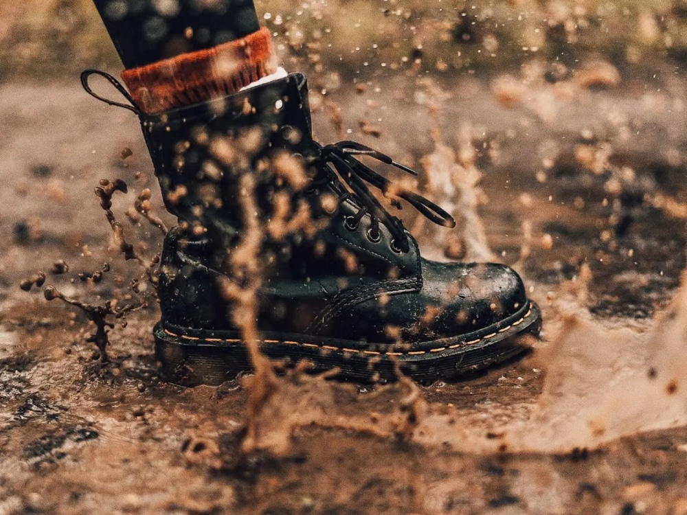 Splashing puddles in boots in the rain