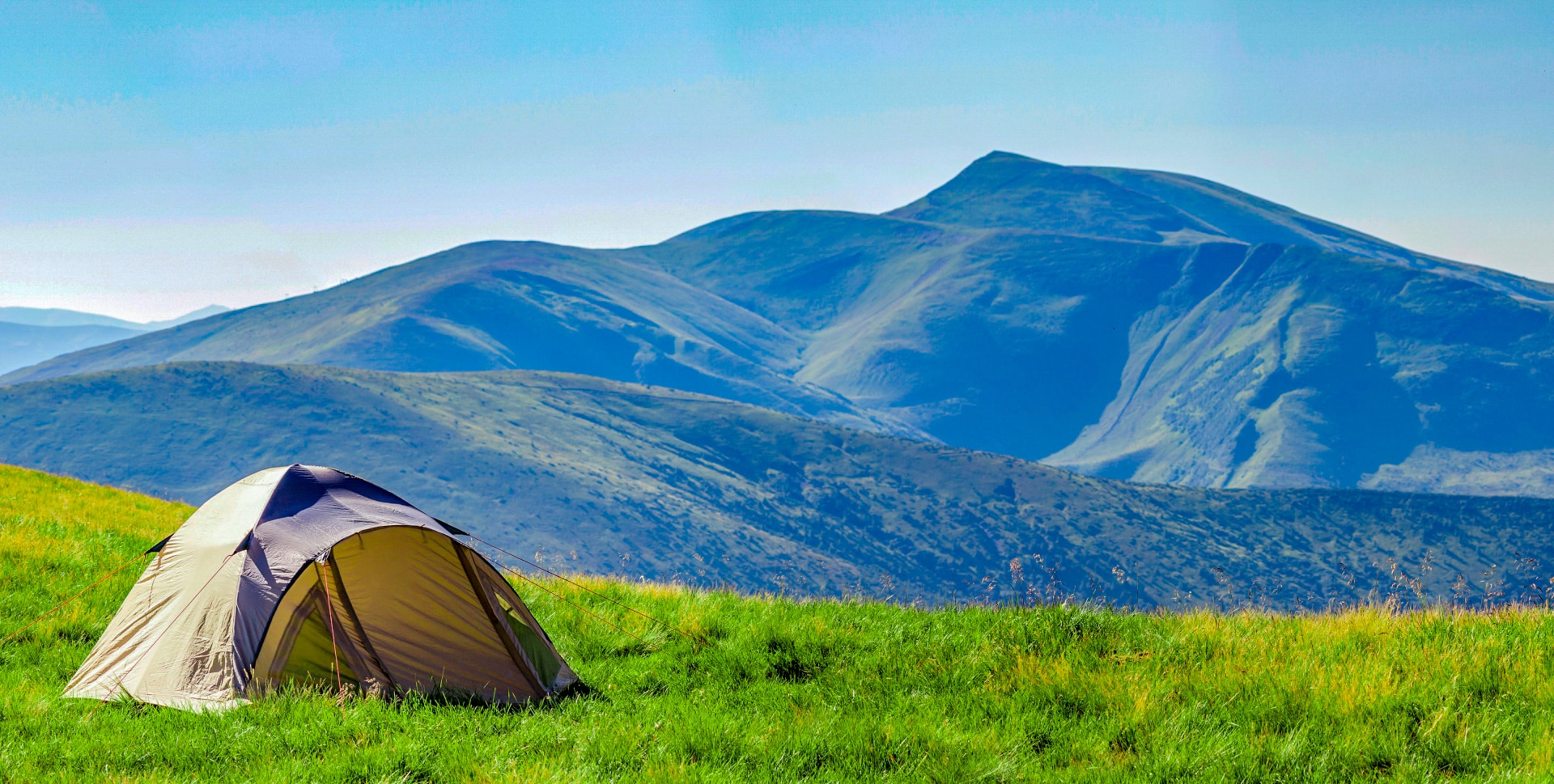 A tent pitched in front of rolling hills