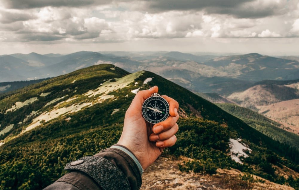 A person using a compass on top of a mountain peak