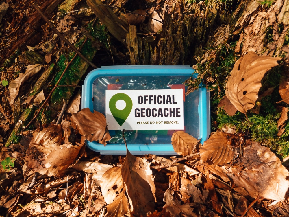 "A blue, resealable box with a sticker reading ""Official Geocache"""