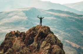 A hiker celebrating reaching the summit after a climb with rolling hills in the background.