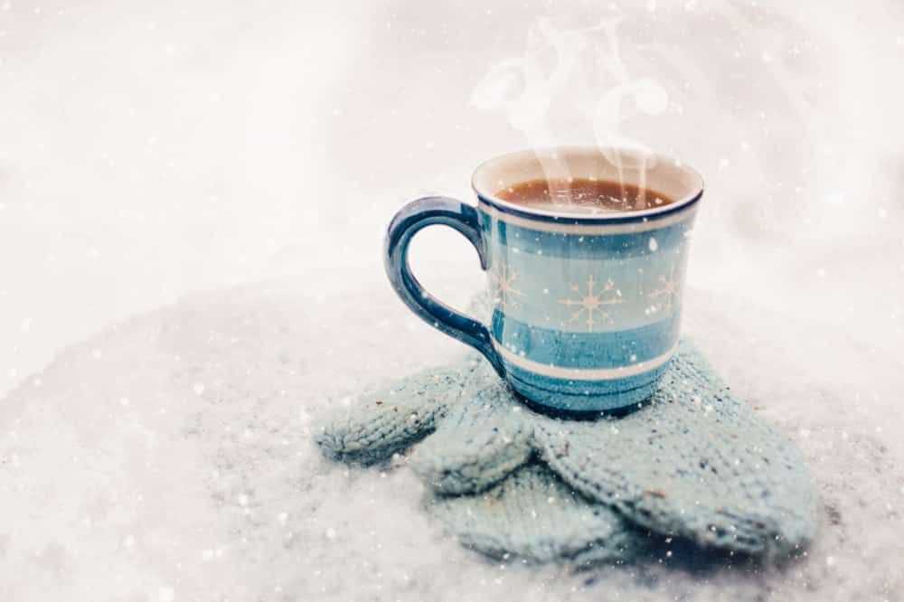 A cup of hot chocolate on a cold snowy morning