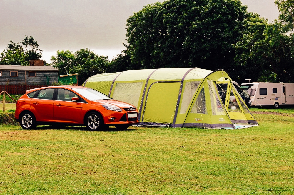 A large family tent at a campsite with a car