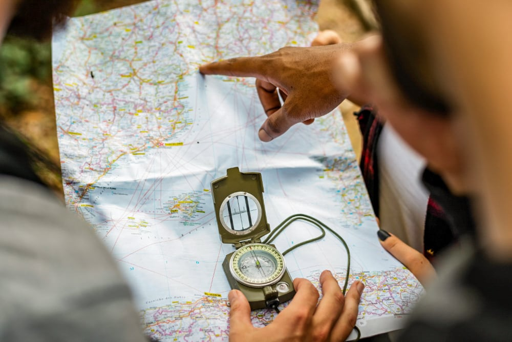 Hikers using a map and compass to find their trail