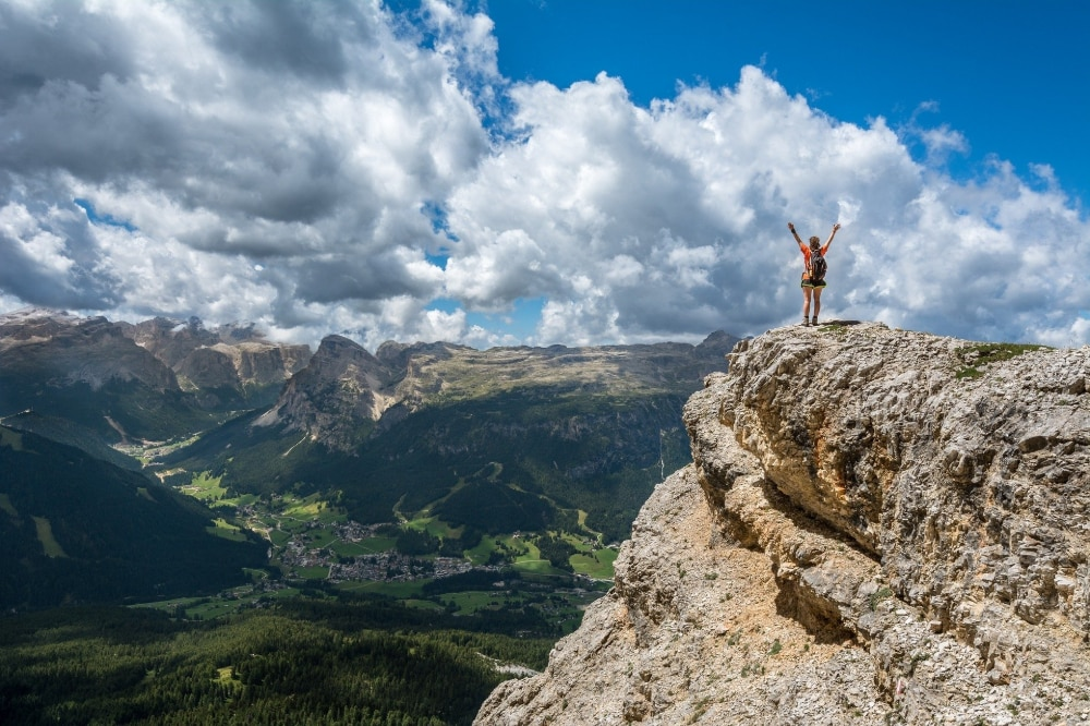 A person celebrates reaching the top of a mountain