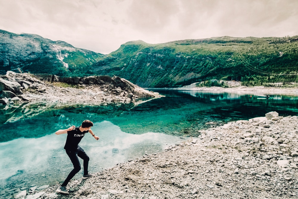 A teenager skimming stones on a lake