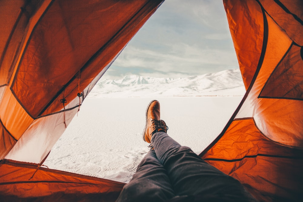 A person sat with their feet out of their open tent looking snow-covered mountains