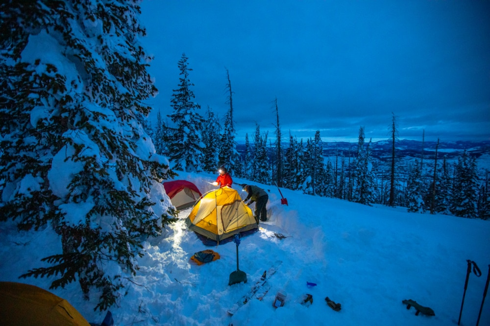 Campers setting up their Battle Mountain tent in the snow