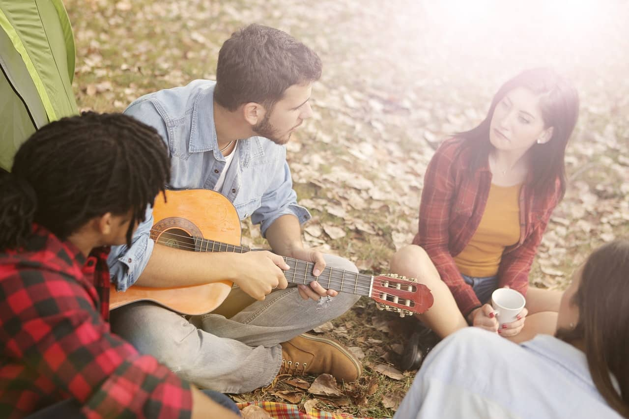 Group of four friends in a circle with a guitar beside a tent