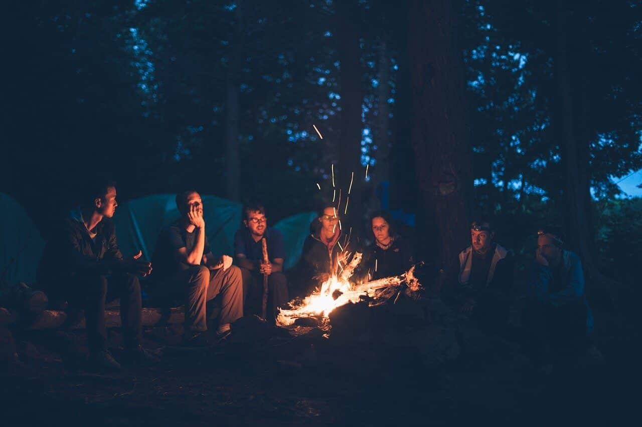 Group of people sitting by a bonfire.