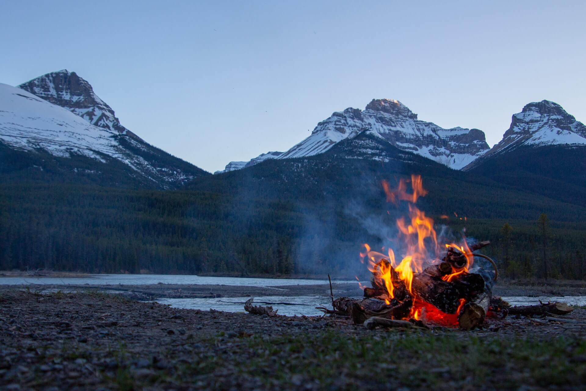 Fire burning in the evening with snow-coated mountains in the background