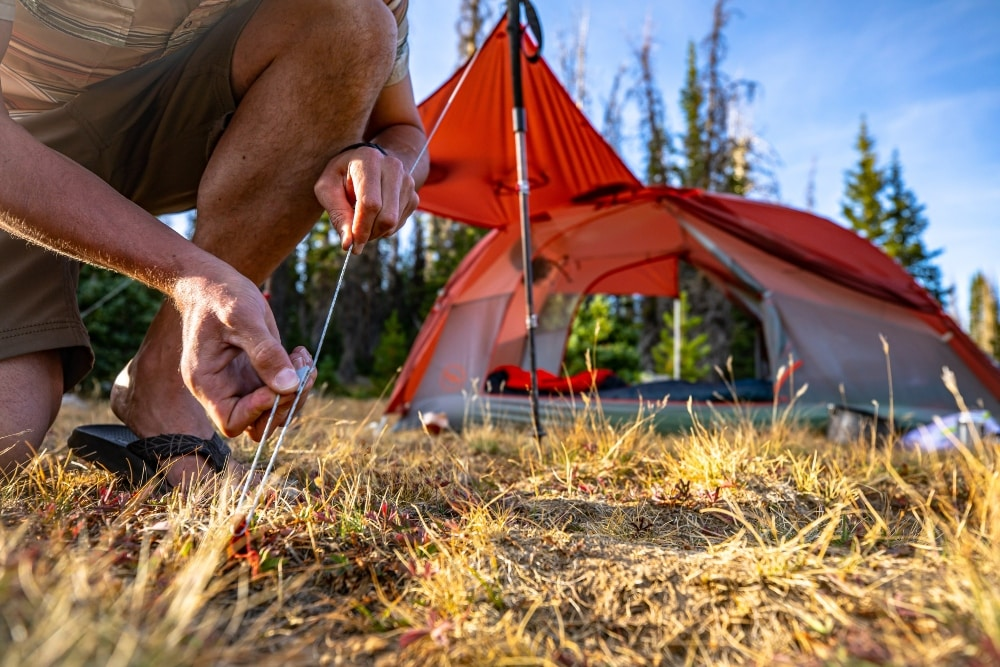 Man pitching the Big Agnes Copper Spur tent by connecting the guyline to the stakes