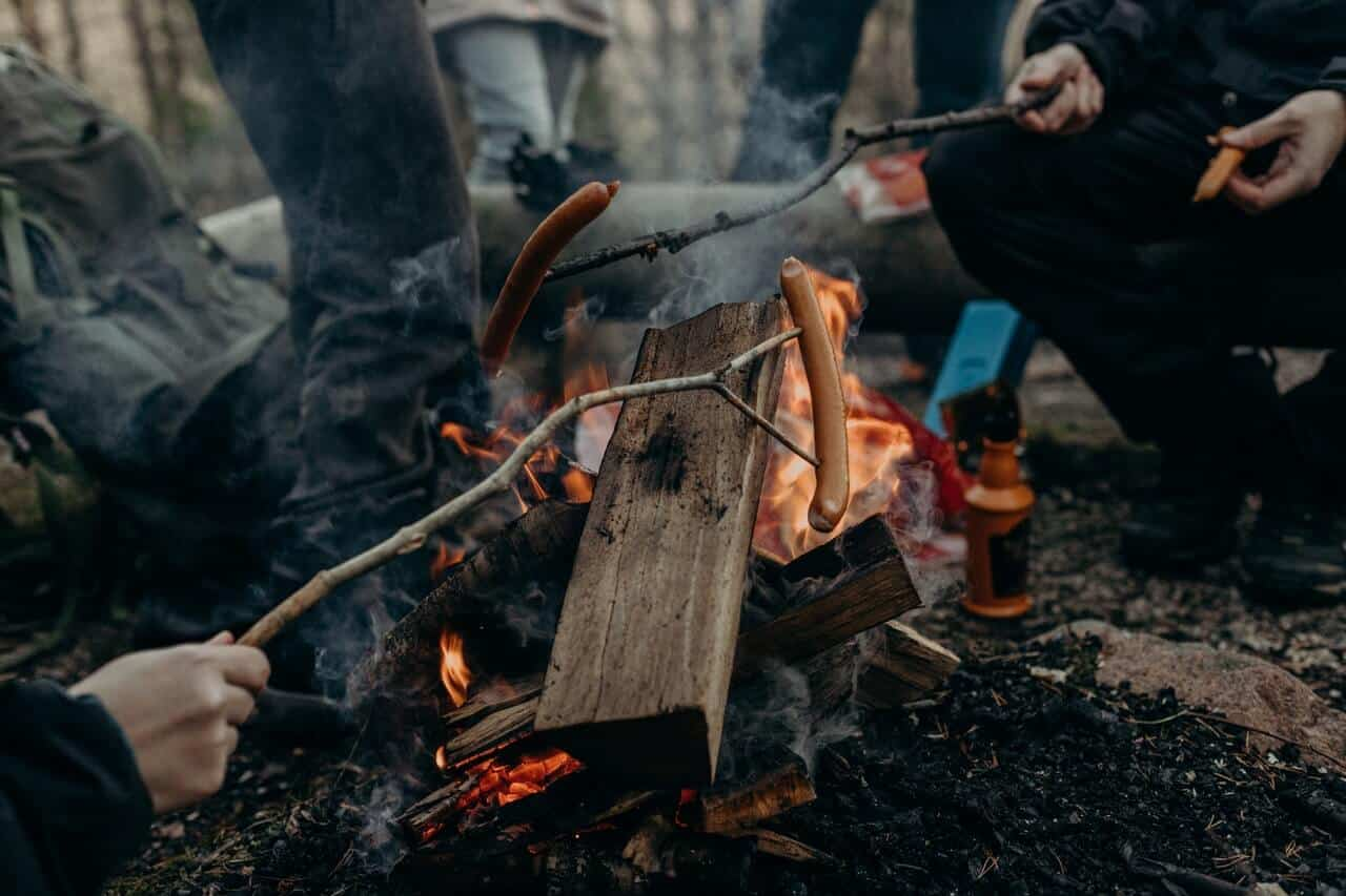 A group roasting sausages over a small fire