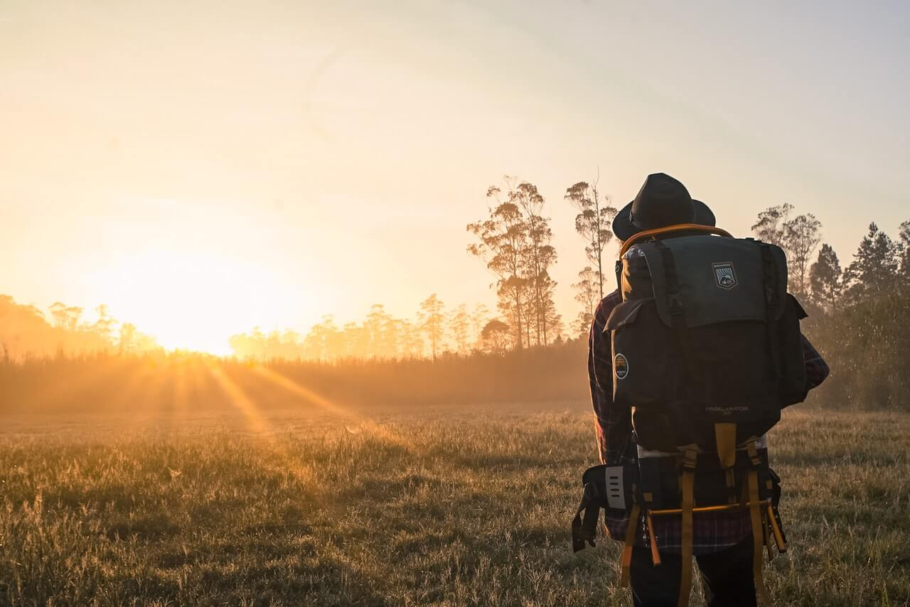 Tall backpacker staring into the sunset