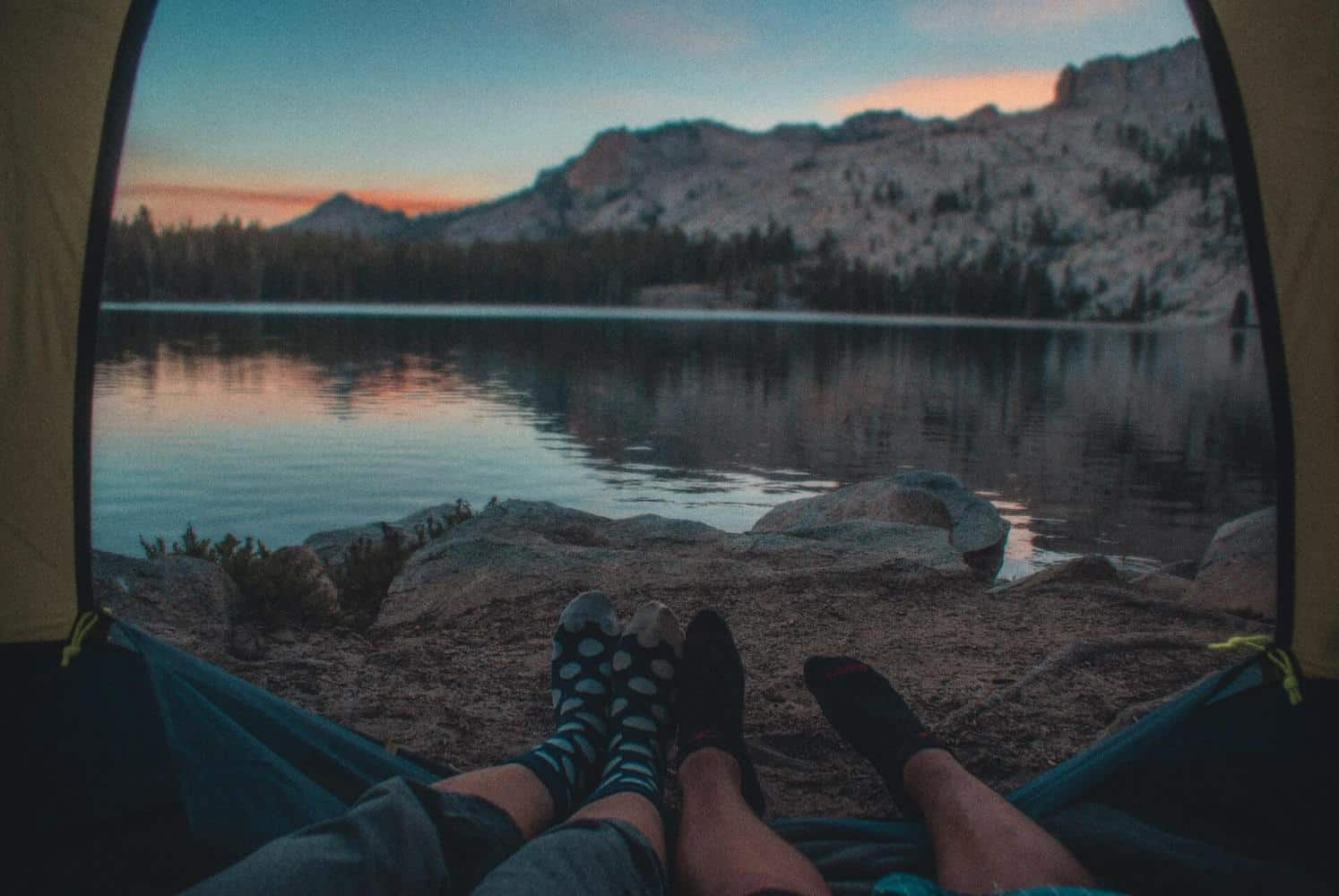 Two people's feet at a tent door with a lake in the background.
