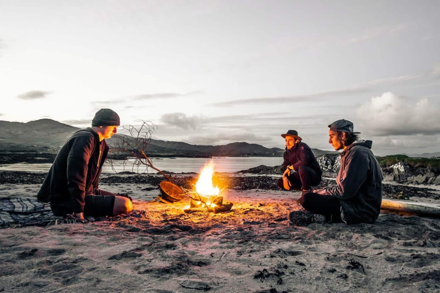 Three people around a campfire