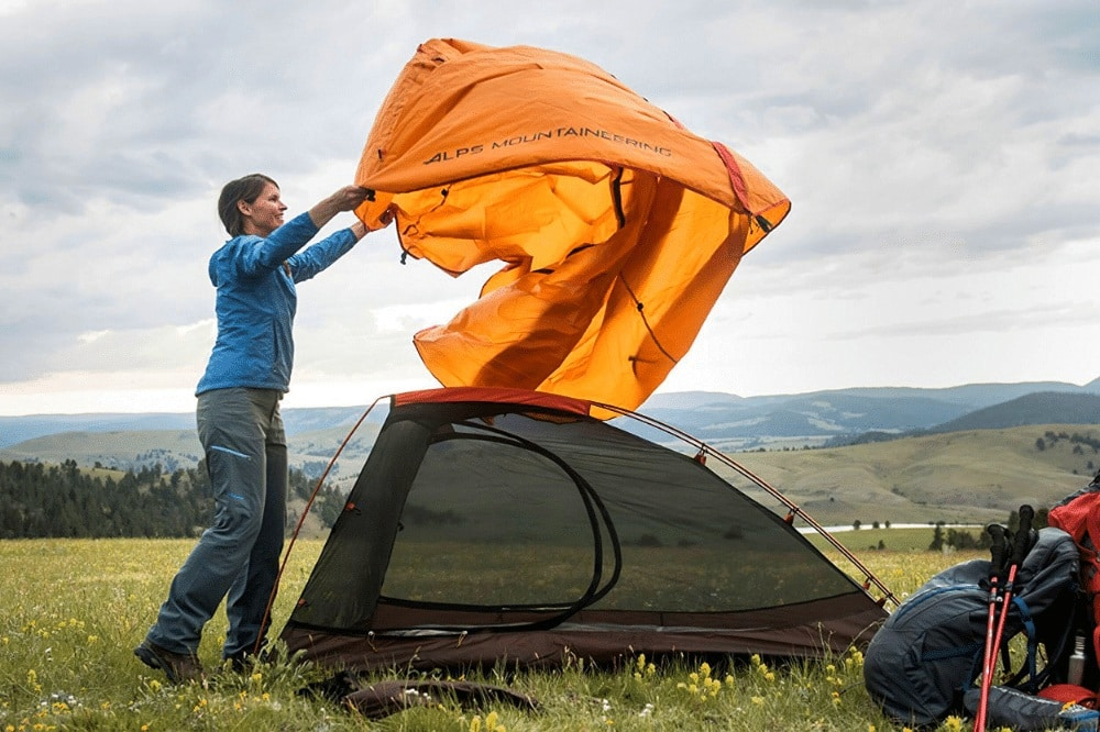 A woman setting up the ALPS Mountaineering Zephyr tent, the best 2 person backpacking and camping budget tent when it comes to storage.