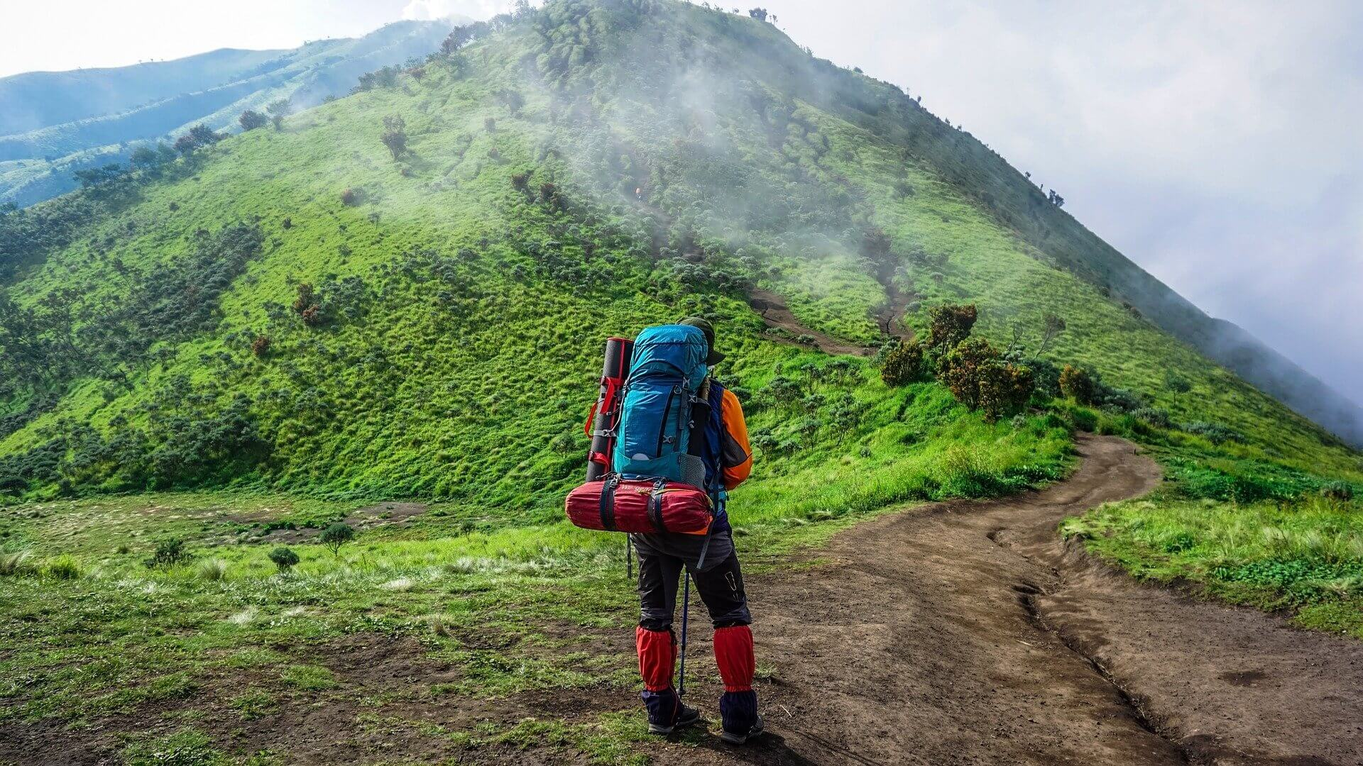 Backpacker on a trail in front of a green mountain.