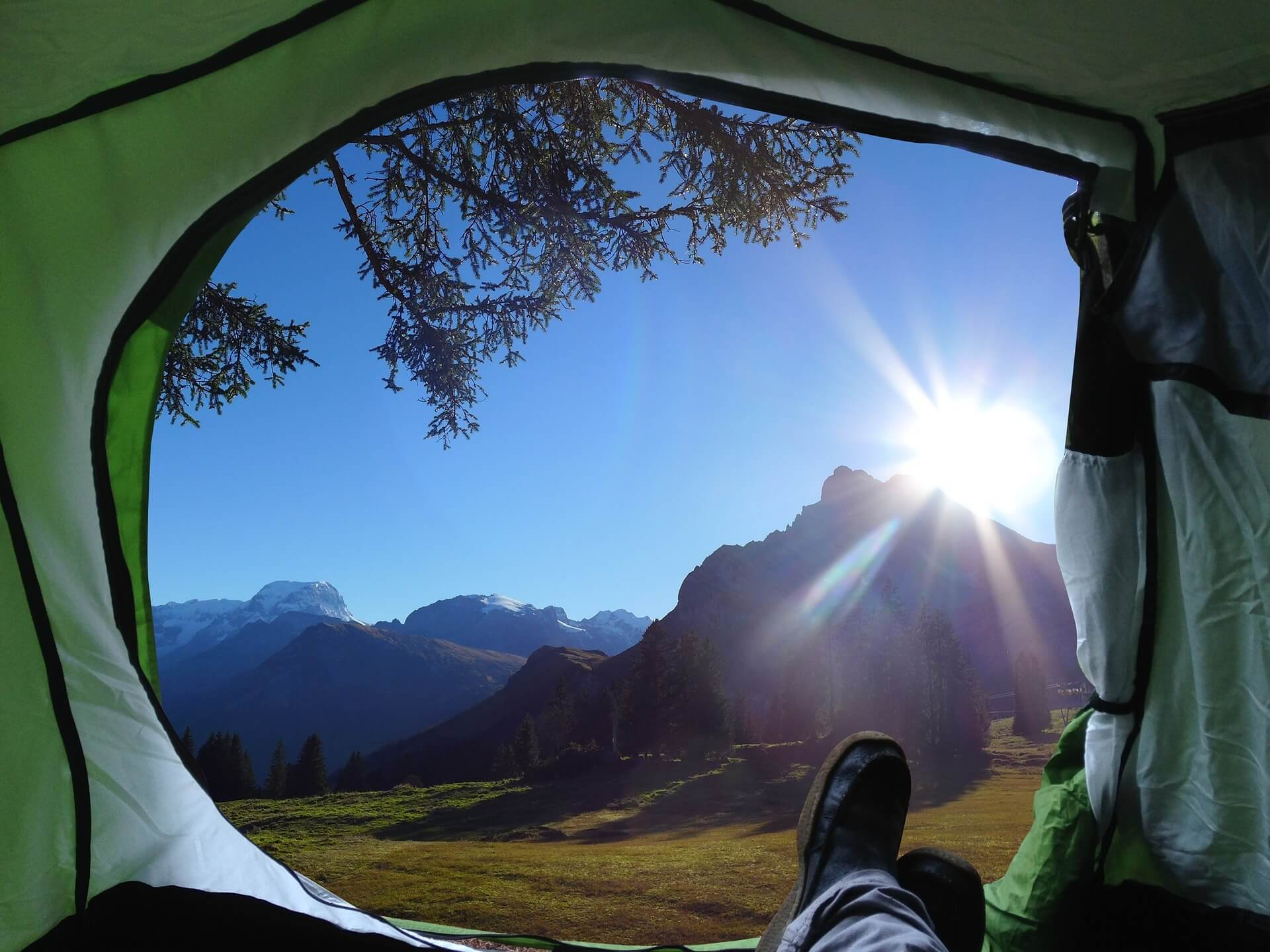 View of nature and mountains from a tent door.
