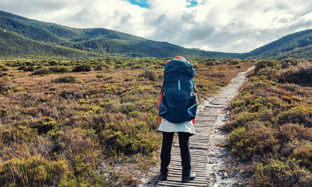 A woman with a backpack on gazing across the hills while she sets off for a day of camping