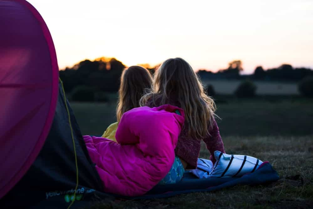 Two girls using the Bundle Bed to sleep under the stars.