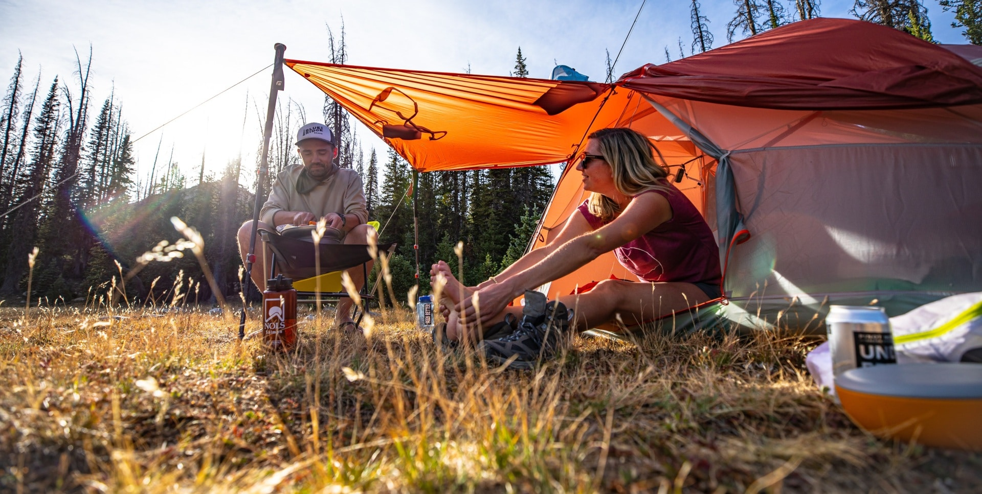 Two campers sat by their Big Agnes Copper Spur backpacking tent