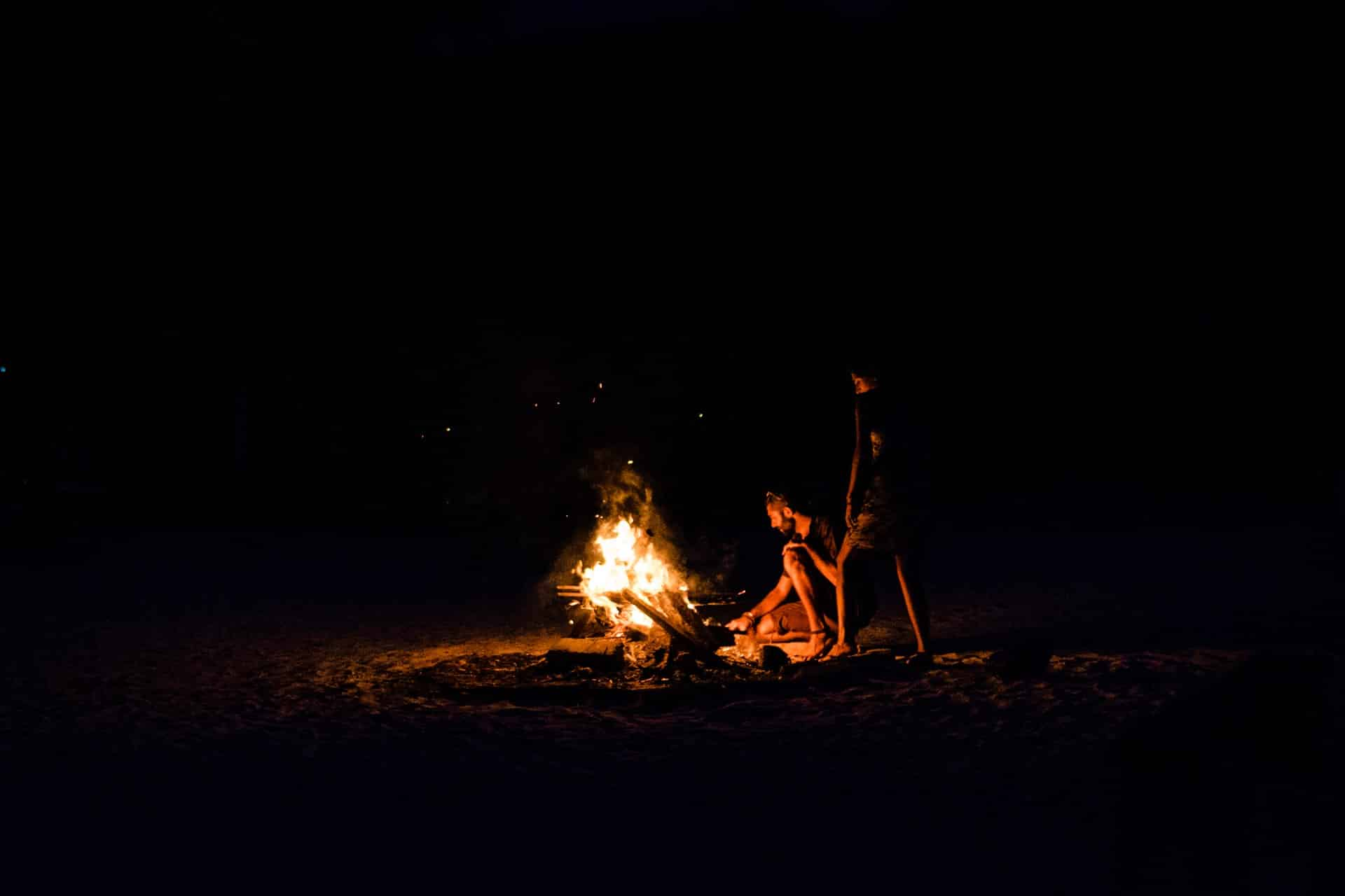 Two people by a campfire at night