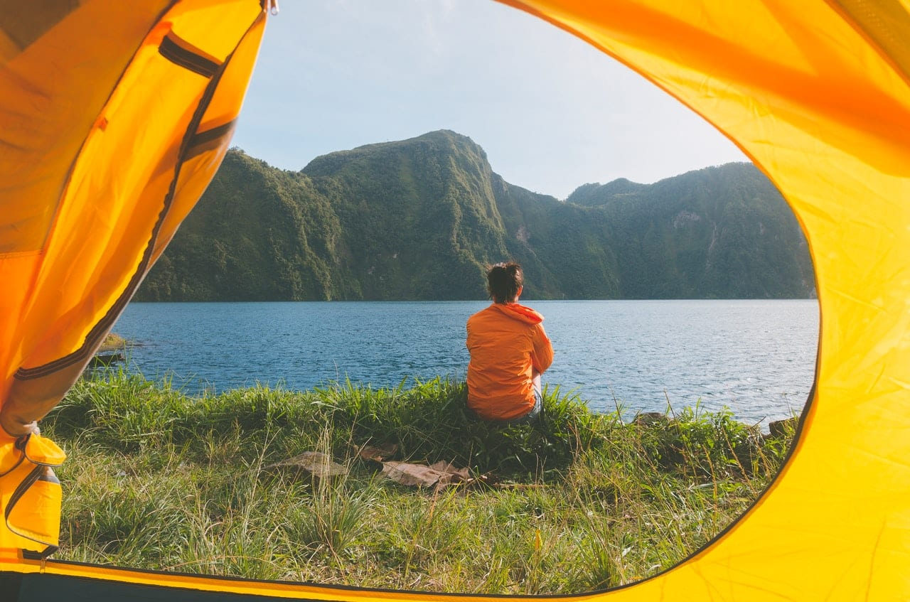A view of a person out of tent doors, sitting by a lake