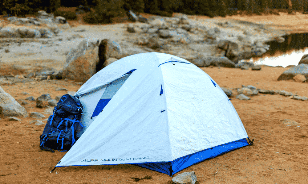 The ALPS Mountaineering Lynx 2-Person Tent set up with a backpack beside it on a shoreline.