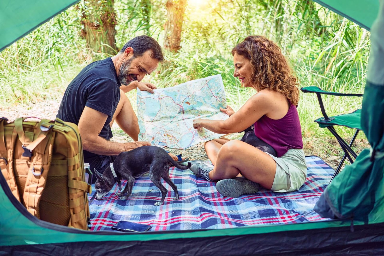 Two people sitting outside a tent holding a map with a dog by their side.