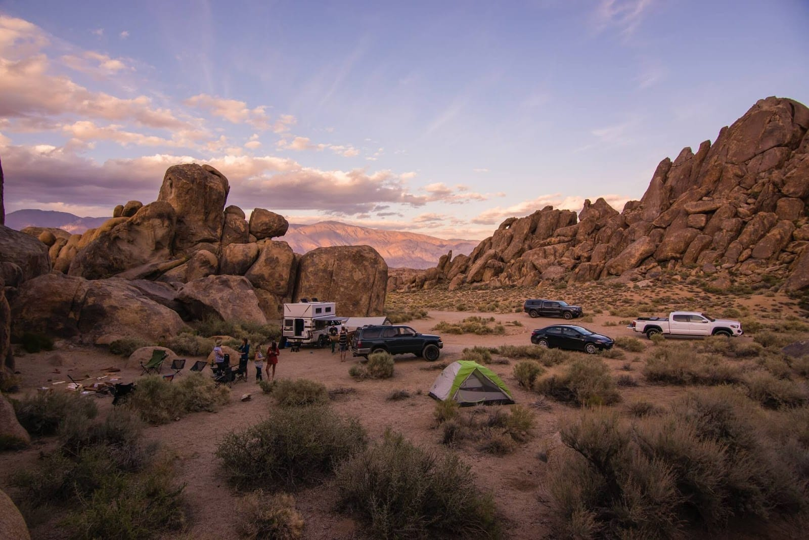 Several tents, cars and people in a desert environment at sunset.