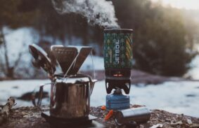 A Jetboil camping stove and a metal coffee pot on the ground with snowy nature in the background.