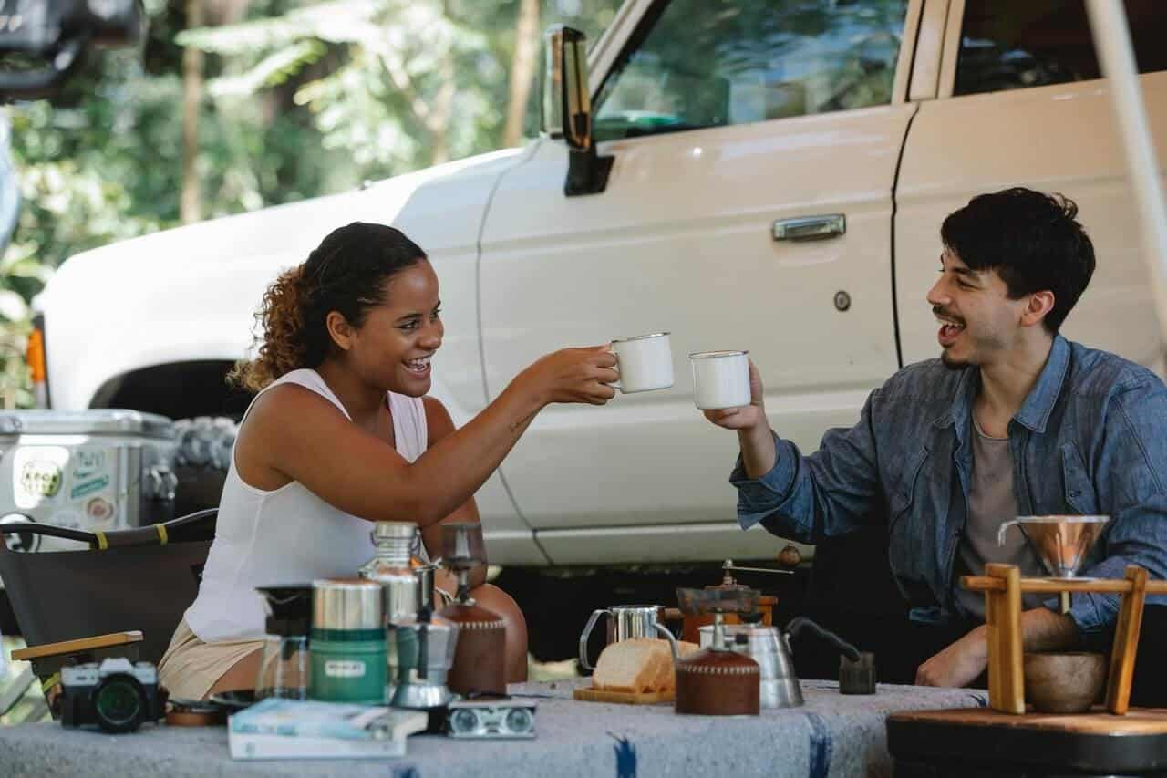 Two people sitting by a pickup truck in nature, having coffee.