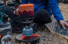 Person sitting on the ground with a Jetboil stove.