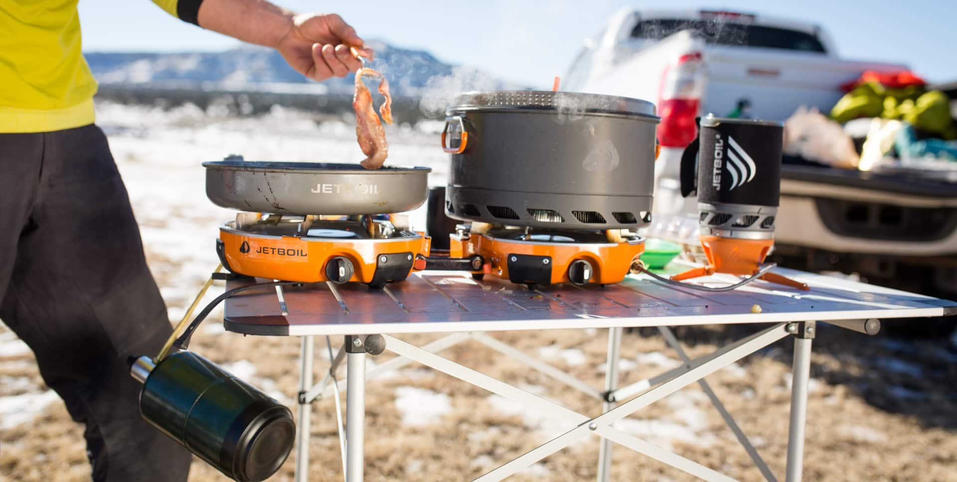 Man frying bacon outdoors on his Jetboil Genesis camping stove