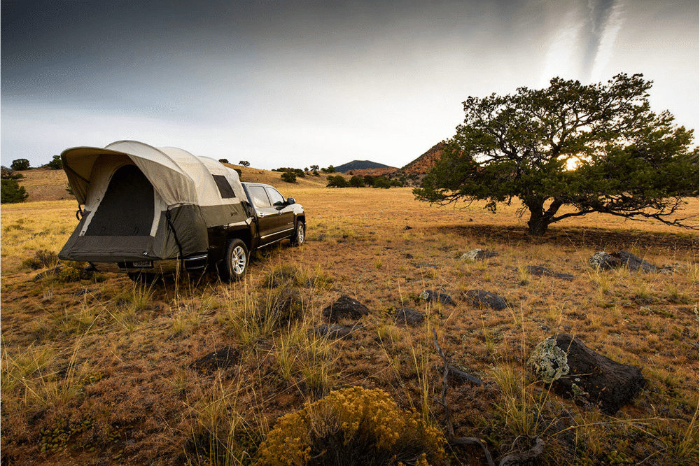 Our pick for best truck tent, the Kodiak Canvas Tent hooked up to a truck while camping in the beautiful outdoors.