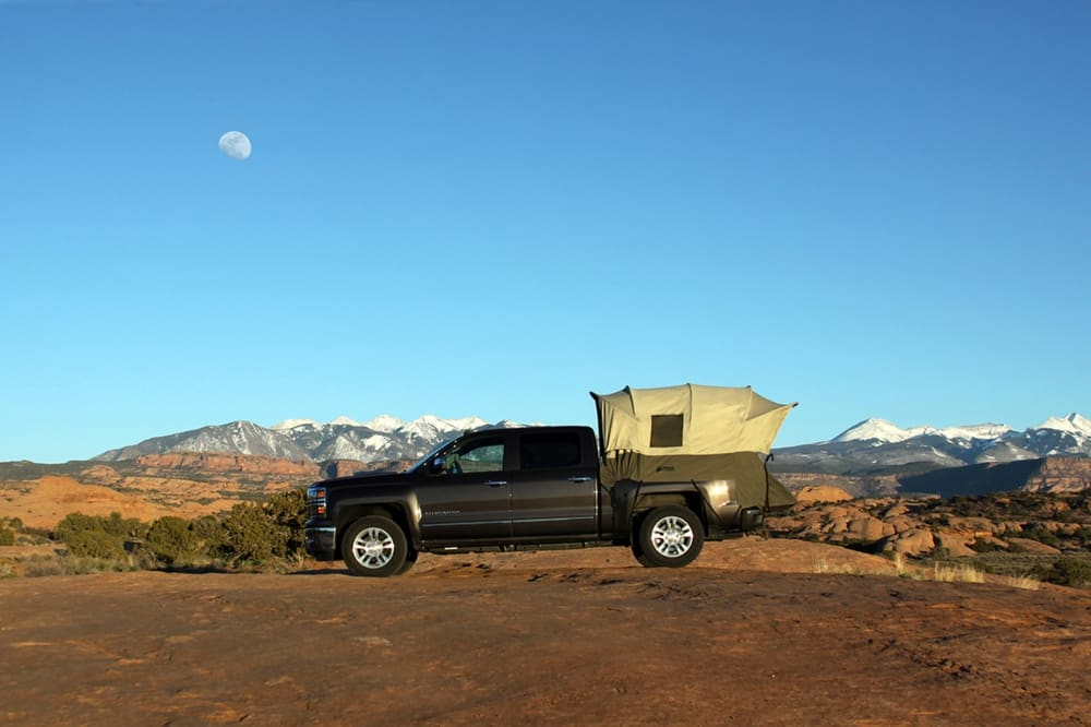 The Kodiak Canvas Truck Bed Tent - the best truck tent overall - fitted to a truck in the middle of outdoor camping