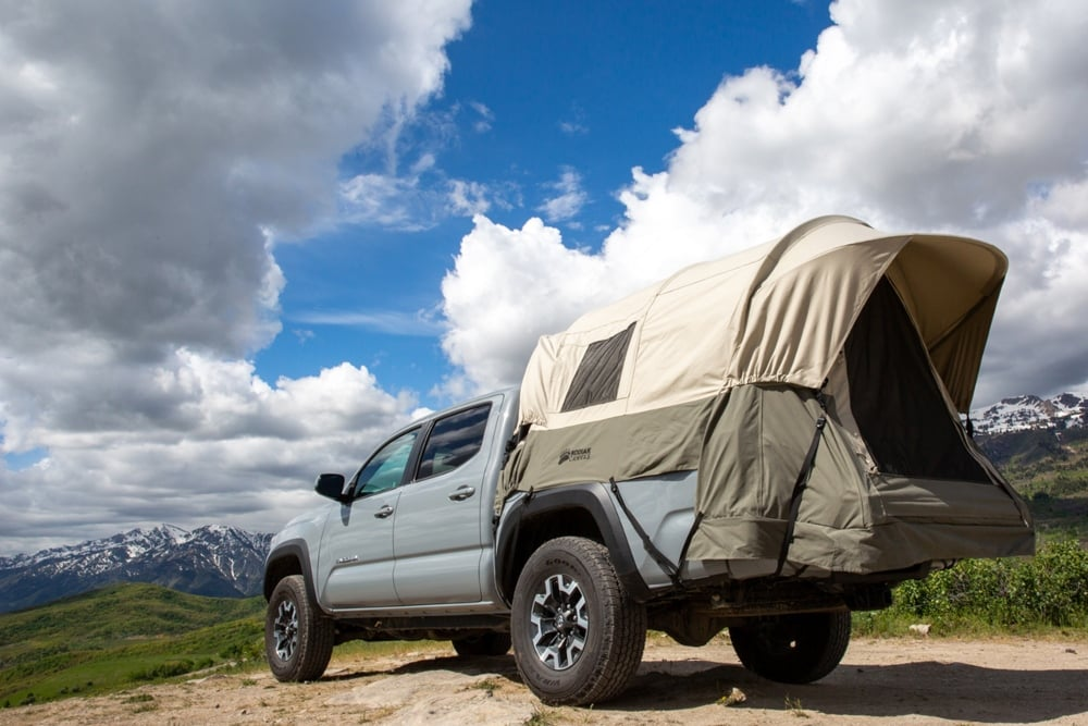 Kodiak canvas truck tent with rainfly on set up for camping on a truck vehicle