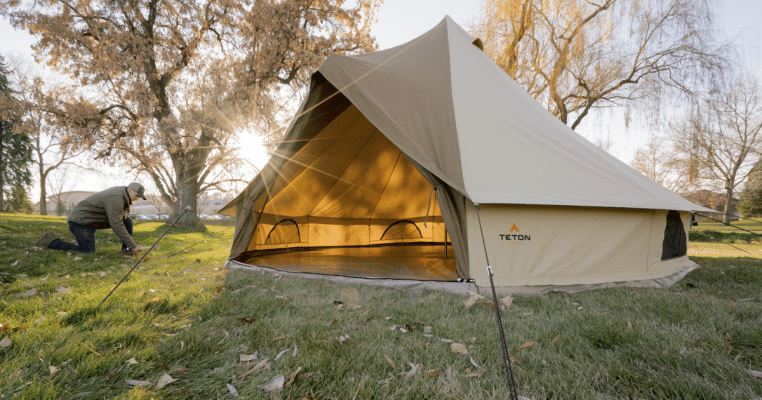 A camper staking down the TETON Sports Sierra canvas tent