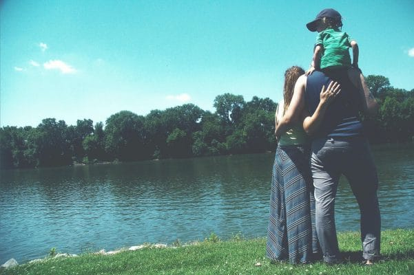 Little family overlooking a lake by a forest